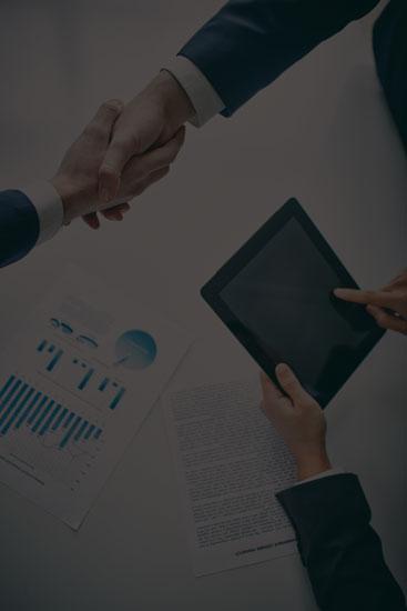 Mãos sendo apertadas ilustrando um negócio sendo concretizado enquanto outra pessoa trabalha em um tablet.