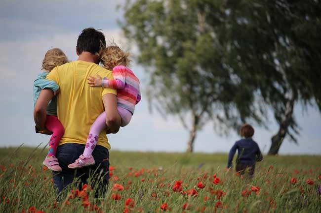 Família andando em um campo de flores, ilustrando a segurança e conforto familiar auxiliado por seguro de vida.